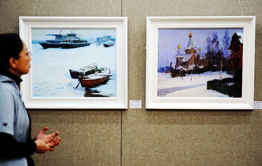 (3)1月9日,一位市民在欣赏冰雪风景油画作品。