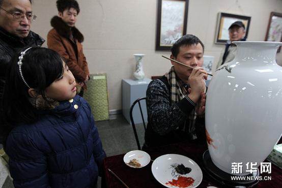 1月12日,观众观看来自江西的高级工艺美术师现场画瓷。新华网图片 任珑 摄
