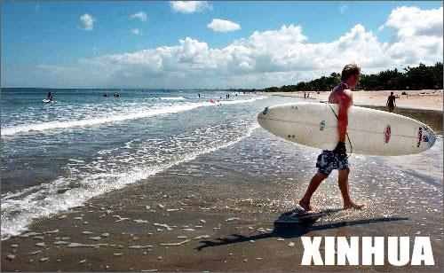 2004年7月30日,在印度尼西亚旅游胜地――巴厘岛的库塔海滩,一名澳大利亚游客抱着冲浪板走回海滩。_巴厘岛的悠闲生活_乐途旅游网