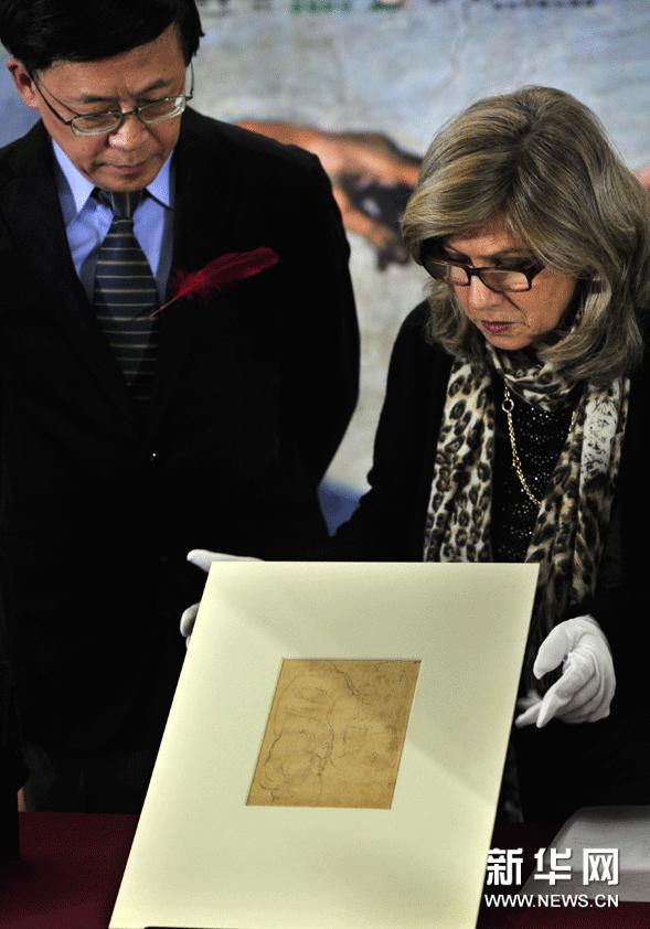1月23日,在台北历史博物馆,来自意大利米开朗基罗故居博物馆的代表(右)展示米开朗基罗手稿真迹《维纳斯像习作》。