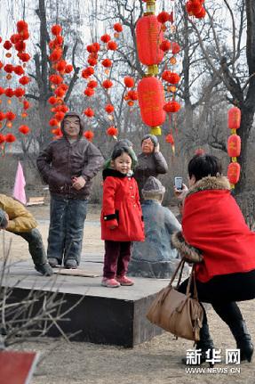 2月23日,在榆次老城新春蜡像展上,一名小朋友在蜡像前留影。新华网图片 王飞航 摄
