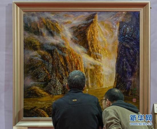 2月28日,参观者在展会上欣赏漆画《峡江》。
