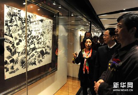 3月4日,借院(右)在艺术展上陪同嘉宾观看其作品。新华网图片 黄本强 摄