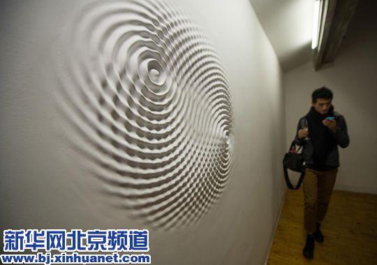 3月28日,一名观众从意大利艺术家劳瑞斯•切克尼的作品《涟漪》旁走过。
