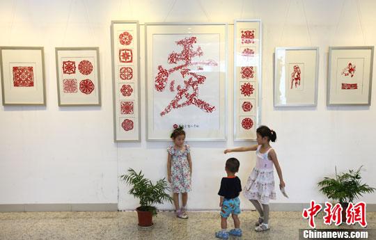 """7月3日,小朋友们被展出的由72个小""""爱""""拼成的大""""爱""""剪纸作品吸引。中新社发 泱波 摄"""
