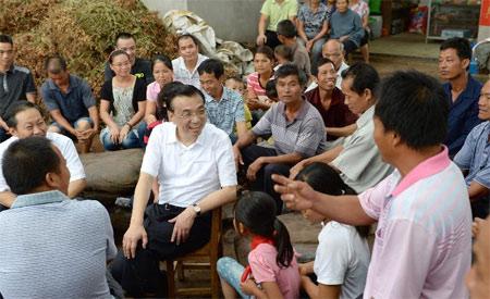 7月9日,李克强在广西南宁坛良村与群众亲切交谈。中共中央政治局常委近期分别到各自的第一批教育实践活动联系点调查研究、了解情况。新华社记者 马占成 摄