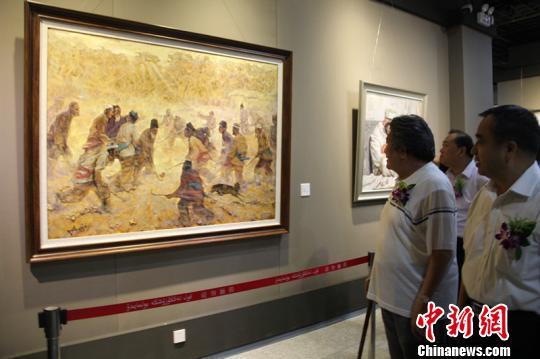"""18日,""""向上•新疆油画作品学术展""""开幕。一幅反应南疆少数民族农民打曲棍球的油画吸引了参观者。 朱景朝 摄"""