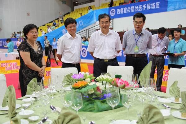 (图二)广西壮族自治区旅游局局长陈建军(右二)等领导看比赛作品。