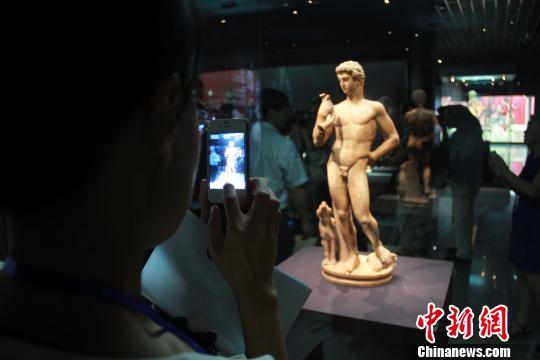 图为游客对雕像进行拍照 记者 张一辰 摄