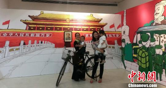 """9月24日,讲述中国人一百年旅行生活的""""国人旅行百年展""""在北京798艺术区开幕。展览现场设有""""拉洋片""""、模型留影区、明信片寄送区、旅行图书角、未来旅行涂鸦墙5个互动区。图为观众在模型留影区开心合影。"""