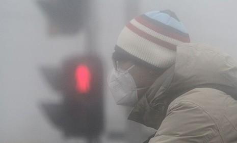 严重的雾霾之下,路人带起了口罩。