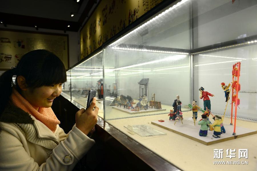 (1)1月6日,在济南市趵突泉公园民俗文化街,游客在用手机拍摄展现元宵节节庆习俗的面塑。