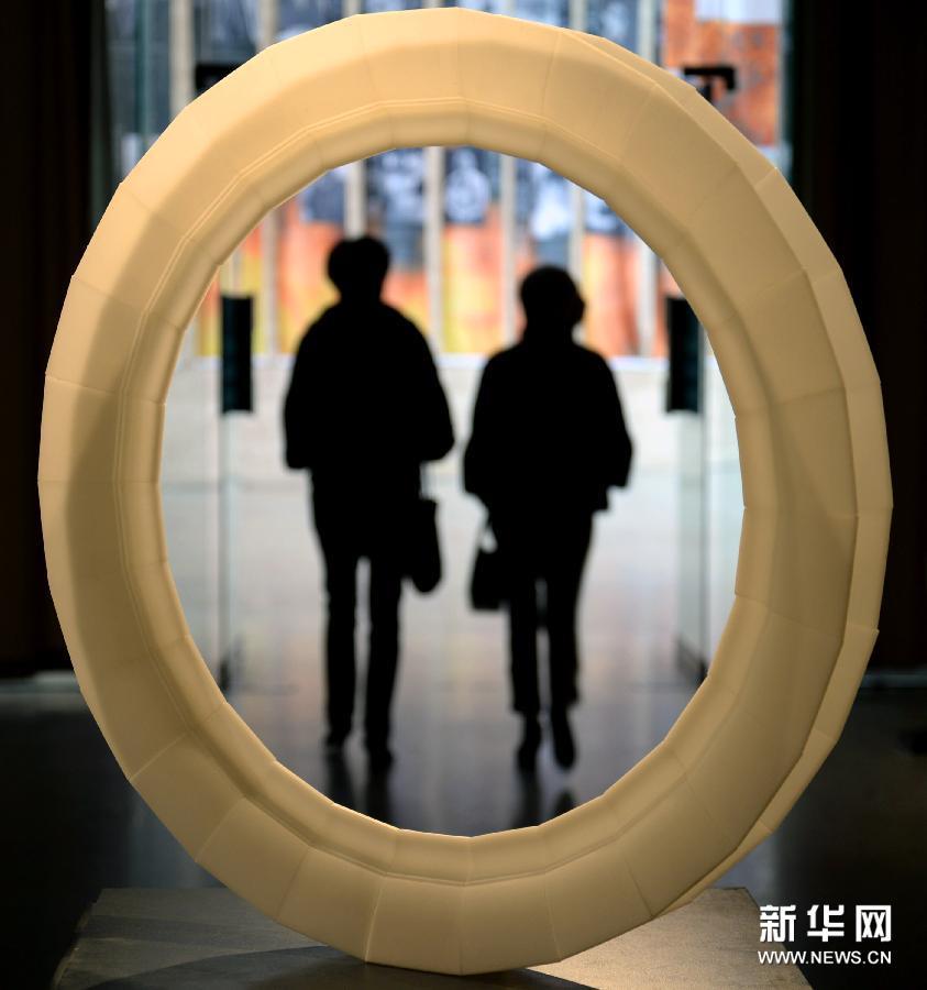 (1)1月13日,在杭州中国美术学院美术馆,参观者从一件名为《蚀刻》的玻璃艺术作品前走过。