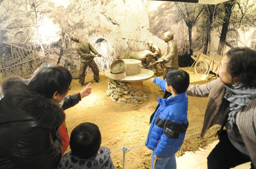 """(2)1月21日,在""""寻根·守望——沐浴圣地洗礼的北京知青""""专题展上,北京老知青在向孙子介绍自己当年在延安的生活经历。"""