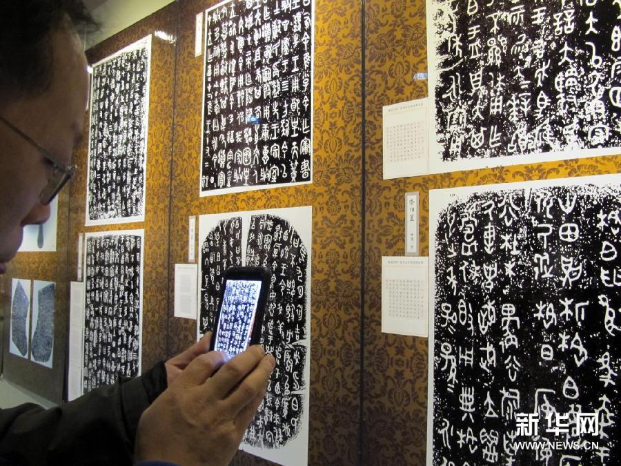 """(1)观众在西安半坡博物馆内""""青铜文明""""书法展上拍摄铭文拓片(1月21日摄)。"""