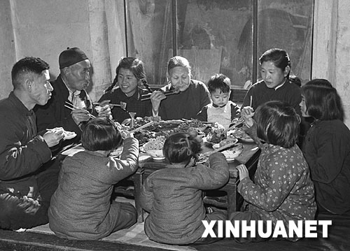 除夕之夜,家人团圆,守岁围炉,温情四溢。图为1953年春节,天津市汉沽区芦台王德铸(左一)一家人吃团圆饭。 新华社发
