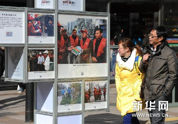 3月5日,游客在北京王府井观看首都学雷锋志愿服务示范站(岗)图片展。新华网图片  罗晓光 摄