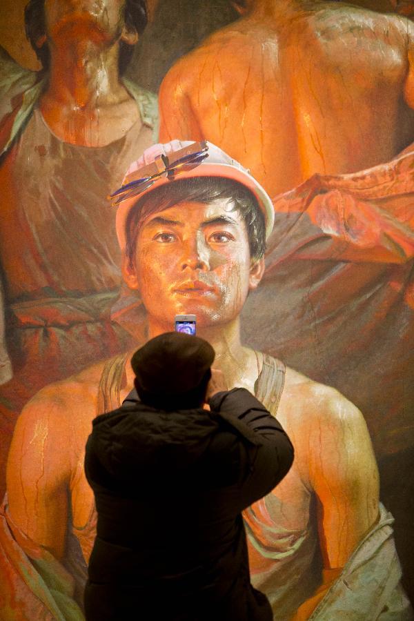 (3)3月7日,一位观众在中国美术馆用手机拍摄广廷渤的油画《钢水·汗水》。