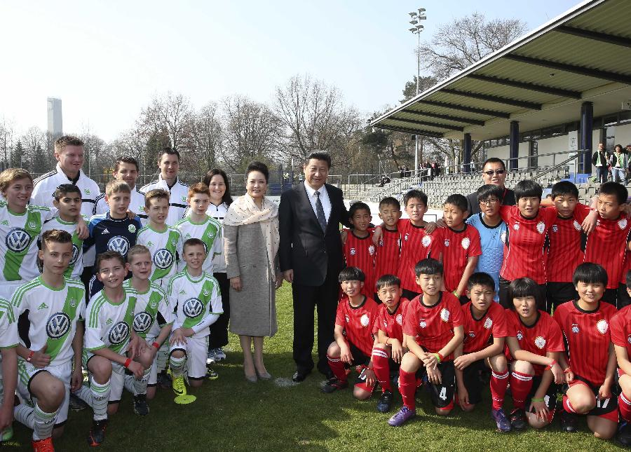 Chinese President Xi Jinping and his wife Peng Liyuan pose for a group photo with Chinese kid footballers and their German peers from the Wolfsburg club in Berlin, Germany, March 29, 2014. (Xinhua/Lan Hongguang)