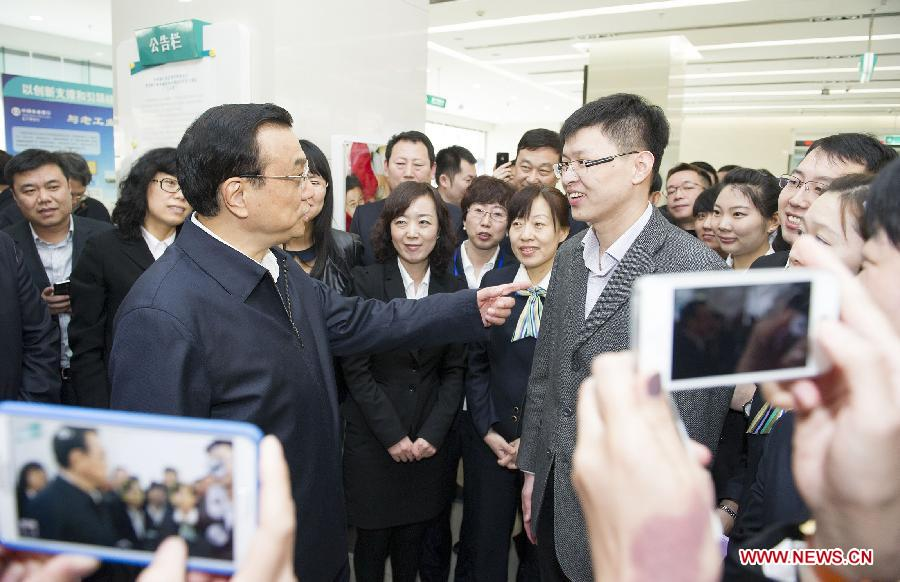 Chinese Premier Li Keqiang (L, front) talks with staff members of the Liaoning Branch of the Agricultural Bank of China in Shenyang, capital of northeast China