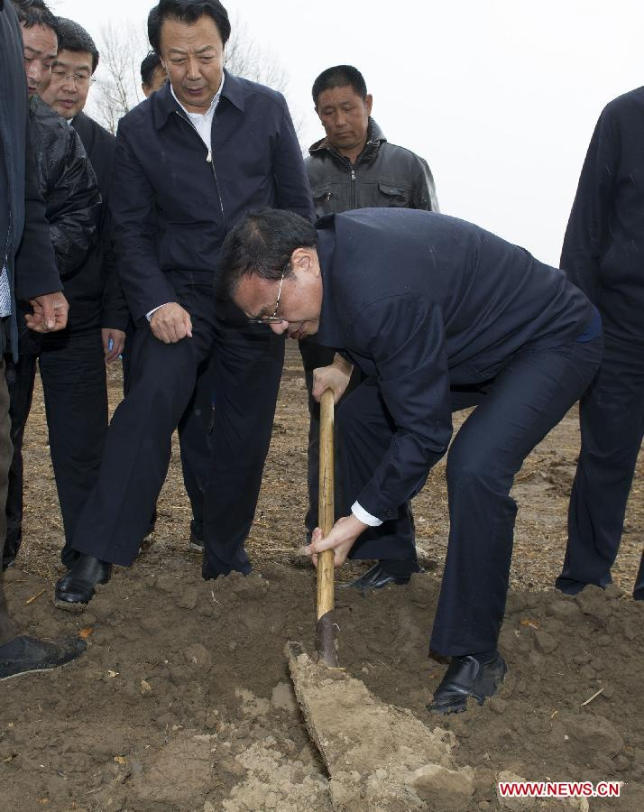 Chinese Premier Li Keqiang (C) examines the farmland soil in Harqin Qi of Chifeng City, north China