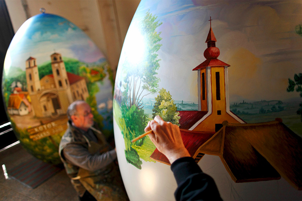 "Croatian painters paint on giant Easter eggs in the style of ""naive"" painting."