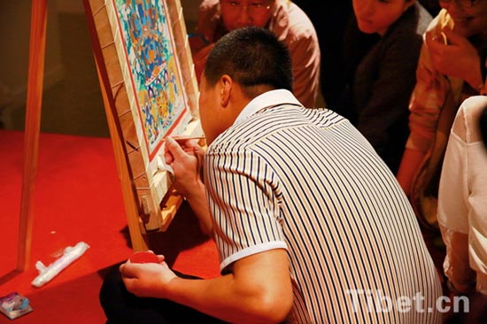 Photo shows a Tibetan artist works on a piece of Thangka painting at the scene during an exhibition held in the National Museum of China. Altogether 65 masterpieces by Nyangbon, an inheritor of Regong Thangka, are on show from April 10 to May 13. Huangnan Tibetan Autonomous Prefecture in Qinghai Province is the hometown of Regong arts, which includes Thangka, murals, paintings and other Tibetan Buddhist art forms. [Photo/China Tibet Online]