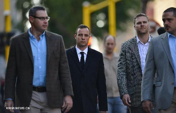 South African Paralympic athlete Oscar Pistorius (2nd L), charged with murder of his girlfriend Reeva Steenkamp, walks to Pretoria