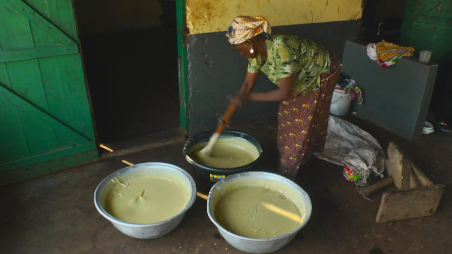 A woman stirring shea nuts paste which is manually made.