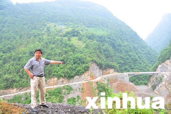 """店子坪村支书王光国指着7月即将正式开通的""""店子坪大桥""""。新华网 曾伟龙 摄"""