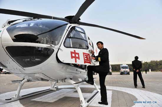 A pilot gets on an ambulance helicopter of the Beijing Red Cross Foundation in Beijing, capital of China, Oct. 28, 2014. The ambulance helicopter, an EC135 aircraft equipped with aerial medical devices, will serve a professional air rescue team of the Beijing Red Cross Foundation. (Xinhua/Li Wen)