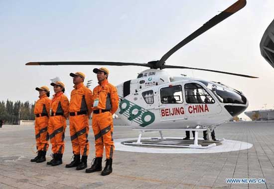 Members of an air rescue team pose for photos with their new ambulance helicopter in Beijing, capital of China, Oct. 28, 2014. The ambulance helicopter, an EC135 aircraft equipped with aerial medical devices, will serve the professional air rescue team of the Beijing Red Cross Foundation. (Xinhua/Li Wen)