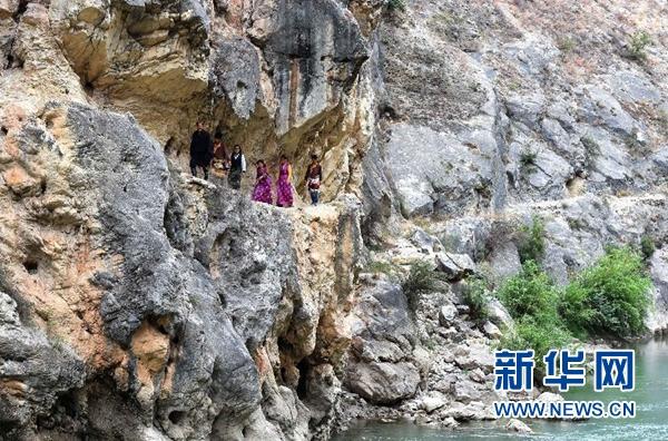 """藏族""""愚公""""斯那定珠传奇斯那定珠(前)和公司的员工走在香格里拉大峡谷内原始的人马驿道上(5月14日摄)。新华社记者王长山摄"""