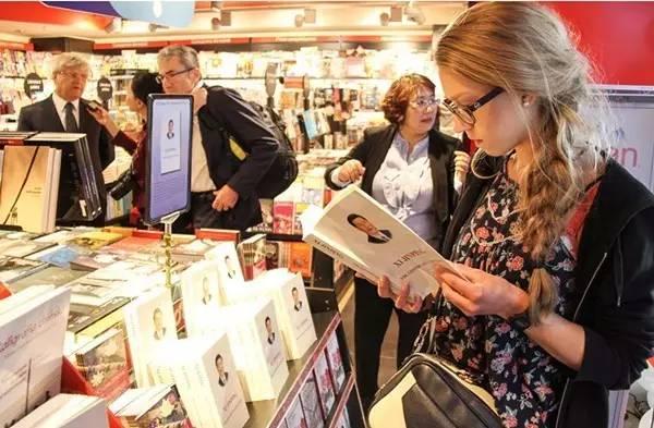 2016年6月14日,一名波兰读者在首都华沙的书店内翻阅《习近平谈治国理政》。新华社记者 陈序 摄