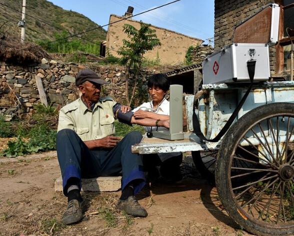 在山西省代县两家店村,刘桂珍在一位村民家中为他测量血压。