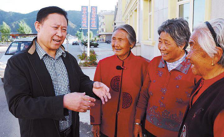 在周台子新村老年公寓,范振喜正在和老人们聊天。