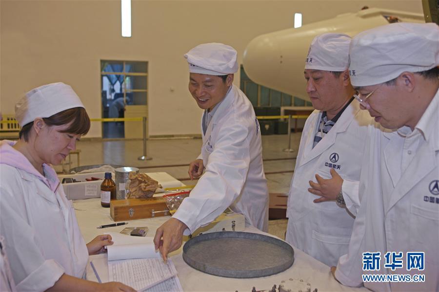 在西昌卫星发射中心总装车间,长三甲系列运载火箭总指挥岑拯(左二)在和科研人员交流(2009年8月11日摄)。新华社发(航天科技集团第一研究院供图)