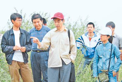 邵明安(中)院士带领学生考察野外试验地。资料照片