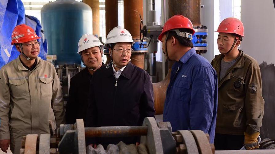 延安市市长薛占海(右三)在大唐延安热电厂东十里铺隔压换热站了解供热管网建设情况。