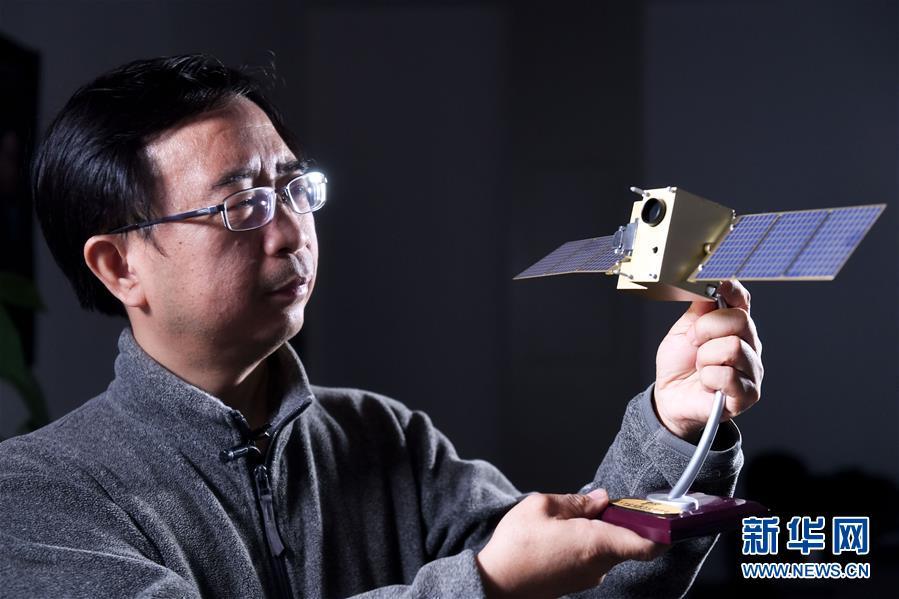 """潘建伟在中国科学技术大学的办公室内与""""墨子号""""量子卫星模型合影(12月13日摄)。"""