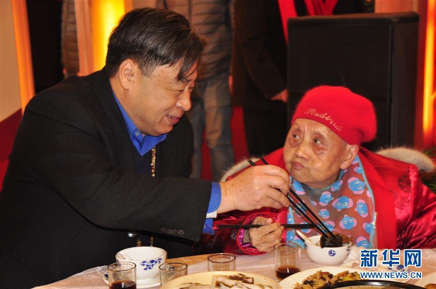 2017年1月21日,茅永红(左)与全国文明家庭代表李声英共享万家宴。新华社发(童汉莲 摄)