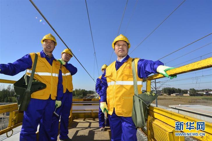 巨晓林(右一)和工友在津保铁路白洋淀站作业现场(2015年10月28日摄)。新华社发(胡斌 摄)