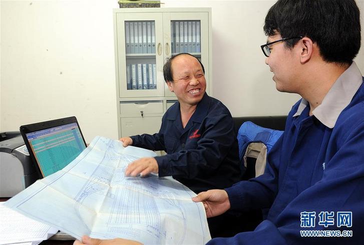 巨晓林(左)在计算机前与徒弟张建观看设计施工图(2012年8月16日摄)。新华社记者 何俊昌 摄