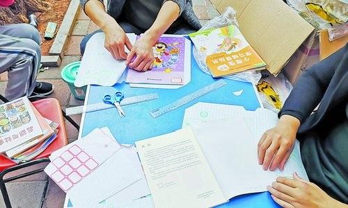 鹭江新城小学附近,一家文具店提供代包书皮服务。