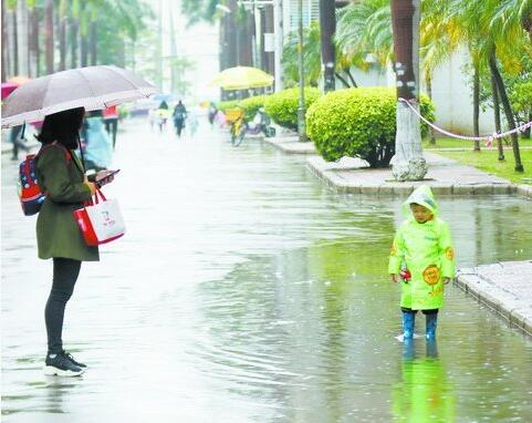 昨日有雨,一名小朋友穿着雨靴在雨中戏水。(