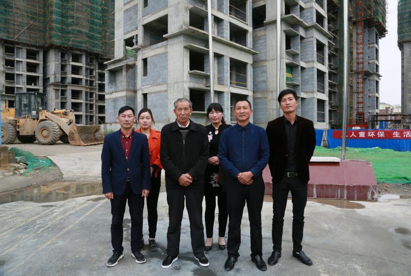 这是晏传忠(前排左二)一家在工地上的照片(合影时二儿子晏家勇不在场。照片由黄久生提供)