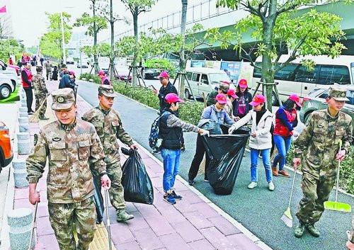 驻区部队与湖里区北站社区的志愿者们一同清理机场附近的道路