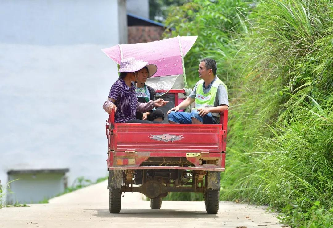 ↑在广西融水苗族自治县杆洞乡锦洞村,驻村第一书记韦斌(右)坐三轮车下村(7月3日摄)。