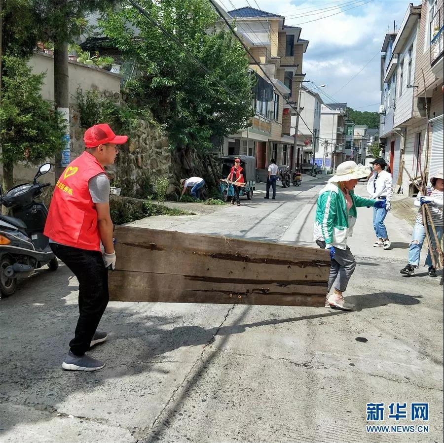 2019年7月,李夏(左)在安徽省绩溪县荆州乡方家湾村走访群众时,帮助村民整治卫生环境。  新华社发