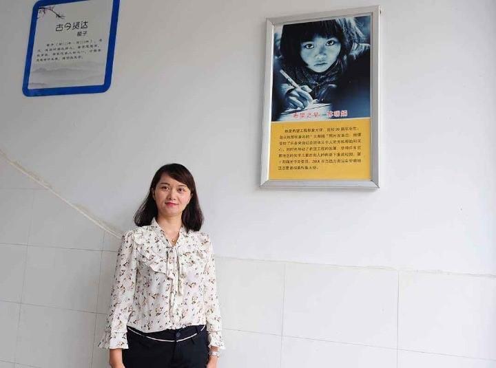 图为:苏明娟与自己当年的希望工程宣传照片合影